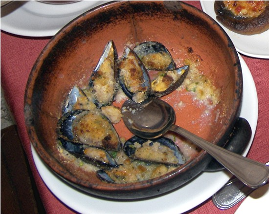 A gratin of mussels blanketed in breadcrumbs and olive oil.